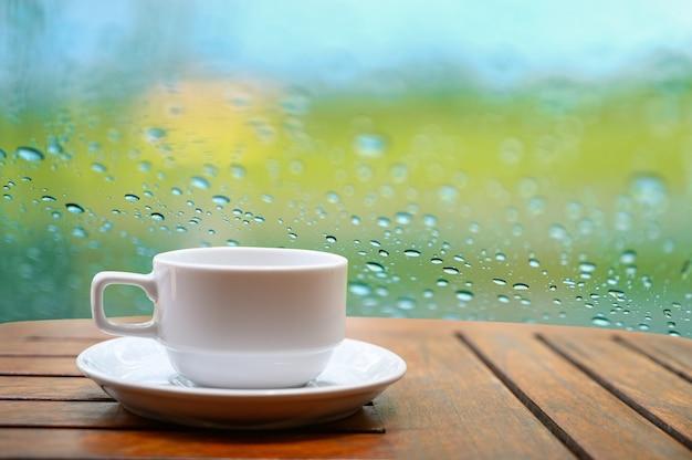 Uma caneca de café branca colocada sobre uma mesa de madeira em um jardim natural