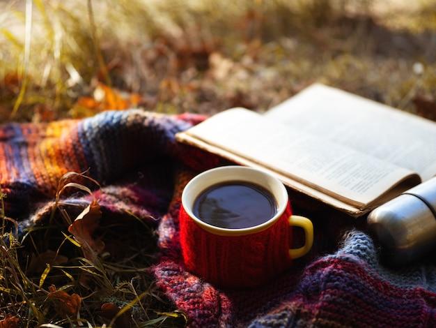 Uma caneca de café quente na folhagem de outono com um lenço de malha colorido e um livro antigo