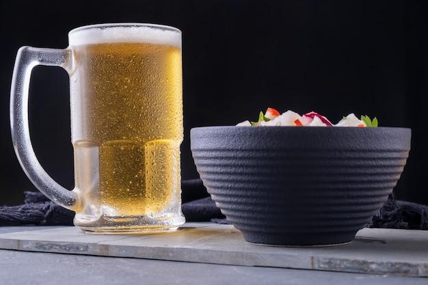 Uma caneca de cerveja gelada e uma tigela de ceviche.