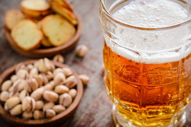 Uma caneca de cerveja light com espuma e pistache em uma mesa de madeira
