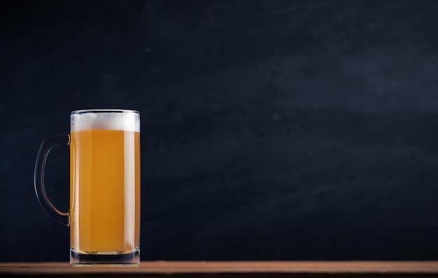 Uma caneca de cerveja não filtrada leve no fundo