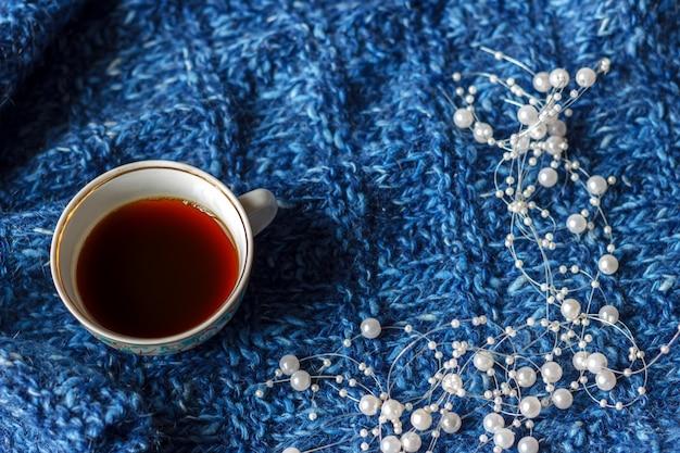 Uma caneca de chá em um fundo azul da malha, o tempo quieto, humor do outono.