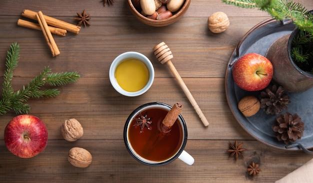 Uma caneca de chá perfumado de maçã de natal com canela em uma mesa de madeira. vista do topo