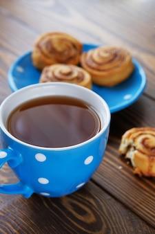 Uma caneca de chá preto e um pão mordido em uma mesa de madeira