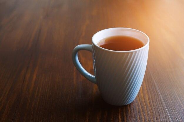 Uma caneca de chá preto em um close-up da mesa de madeira escura.