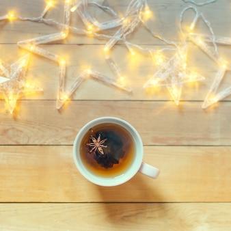 Uma caneca de chá quente com especiarias em um fundo de madeira com guirlanda de natal.