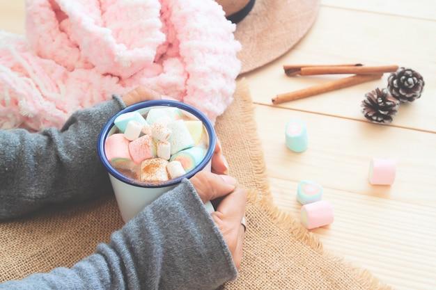 Uma caneca de chocolate quente com marshmallows pastel nas mãos da mulher. estilo de vida acolhedor.