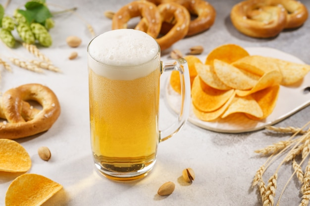 Uma caneca de chope e vários petiscos ao redor - pretzels, batatas fritas e pistache.