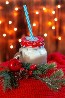 Uma caneca grande com chocolate e marshmallow em um lenço vermelho com um galho de árvore de natal