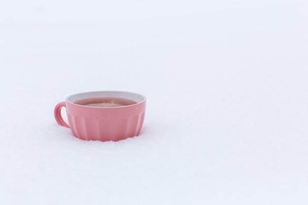 Uma caneca rosa com uma bebida está de pé na neve em uma rua no inverno