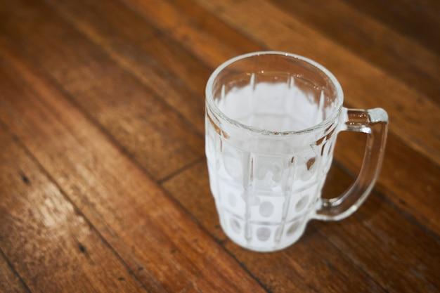 Uma caneca vazia de cerveja coberta com gelo está sobre uma mesa de madeira de um pub