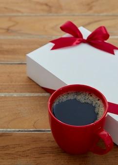 Uma caneca vermelha café e caixa de presente em madeira