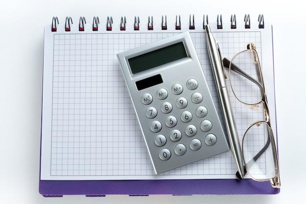Uma caneta, calculadora e óculos encontram-se em um bloco de notas aberto. ao lado do laptop. uma folha de caderno em branco com os itens de um empresário ou contador