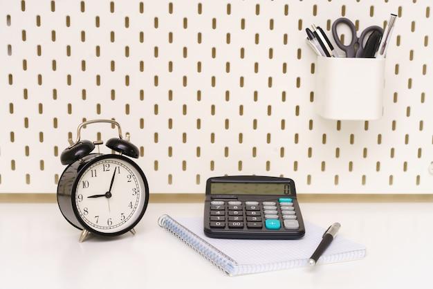 Uma caneta de bloco de notas de despertador preto e calculadora são colocados em um fundo branco da mesa cinco mi ...
