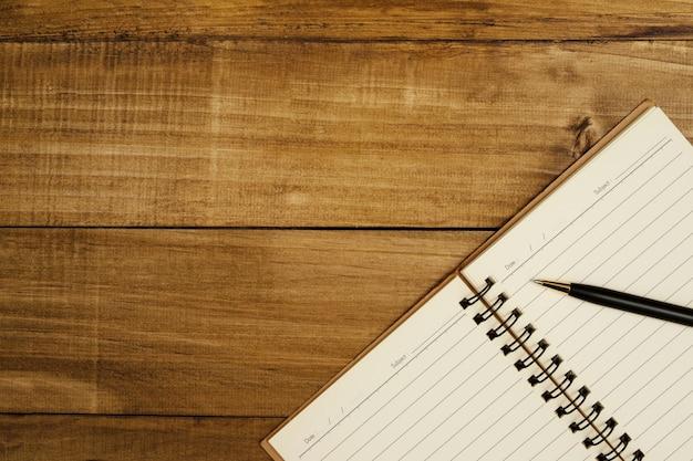 Uma caneta é colocada em um caderno aberto esperando para fazer anotações.