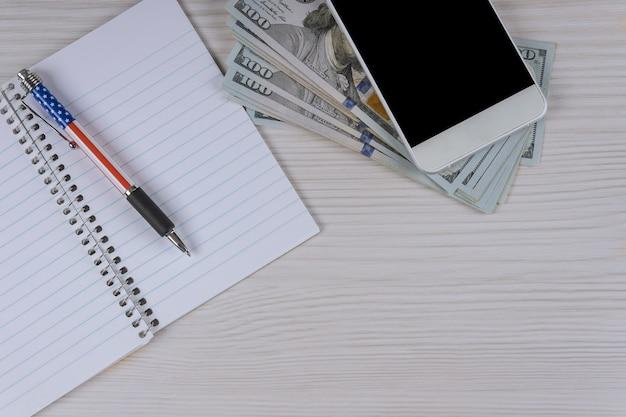 Uma caneta e notas de dinheiro em dinheiro em um caderno