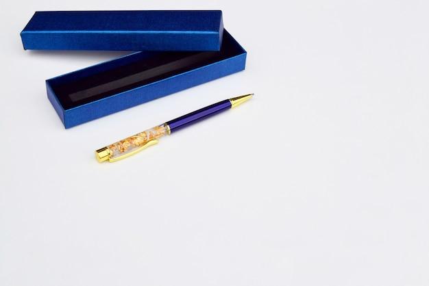 Uma caneta e uma caixa de presente azul para um close-up de caneta, em um fundo cinza