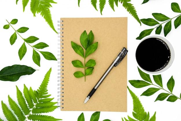 Uma caneta em um livro com folha verde isolada no fundo branco
