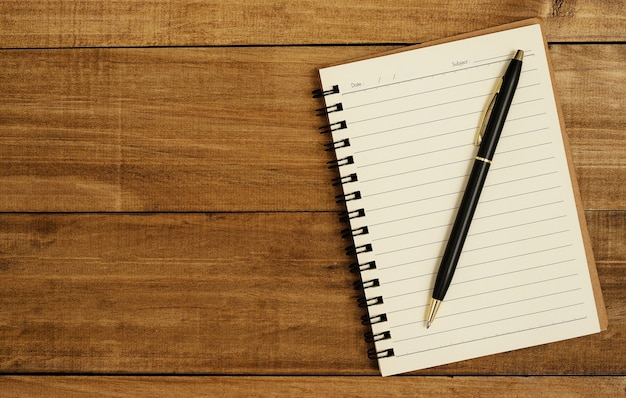 Uma caneta preta é colocada no caderno.
