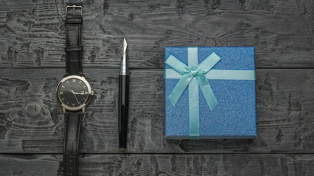 Uma caneta-tinteiro, um relógio masculino e uma caixa de presente azul em um pescoço de madeira