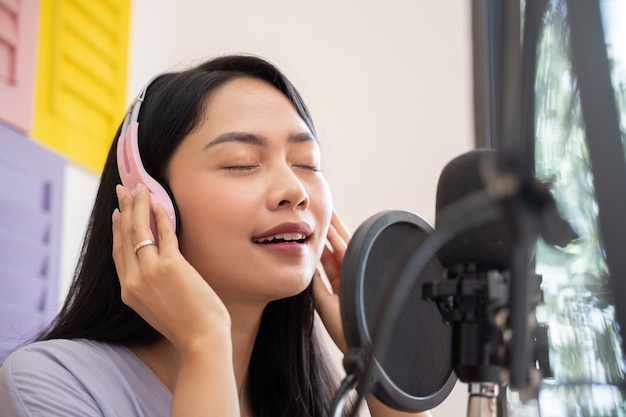 Uma cantora asiática usando e segurando fones de ouvido enquanto canta