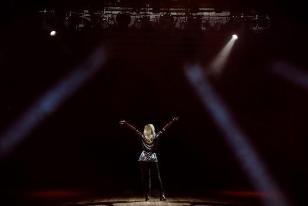 Uma cantora jovem no palco durante uma vista de concerto na parte de trás.