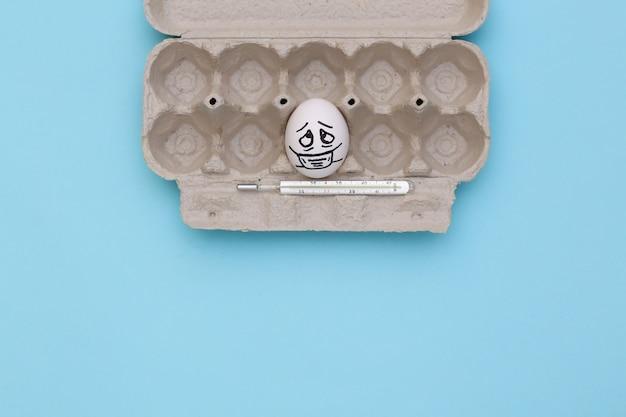 Uma cara de ovo em máscara médica com termômetro na bandeja sobre fundo azul. pandemia do covid19. vista do topo