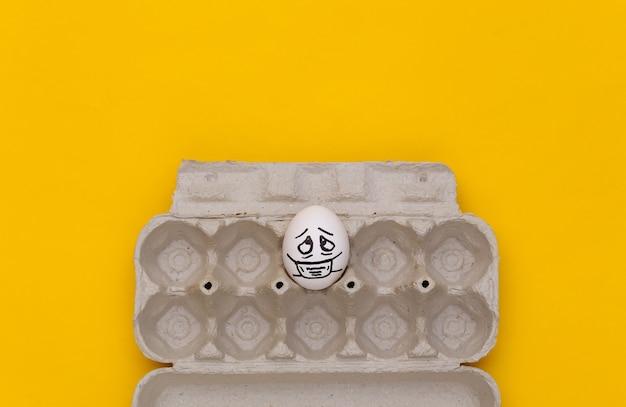 Uma cara de ovo em máscara médica na bandeja em fundo amarelo. pandemia do covid19. vista do topo