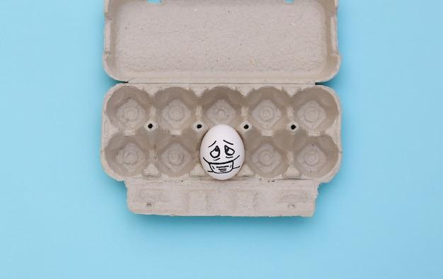 Uma cara de ovo na máscara médica na bandeja sobre fundo azul. pandemia do covid19. vista do topo