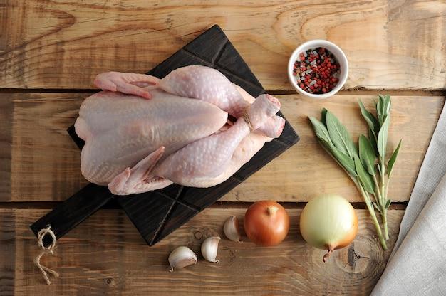 Uma carcaça de frango cru inteiro com pés de barbante associados na superfície rústica de madeira