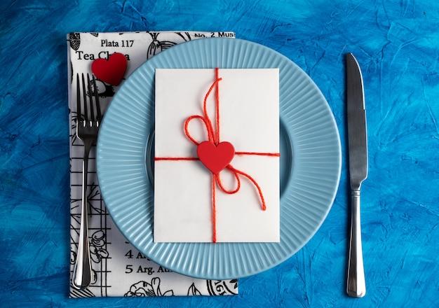 Uma carta com um coração em um prato azul