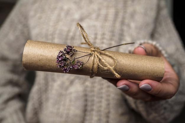 Uma carta decorada com uma flor de orégano nas mãos de uma menina