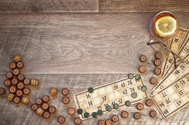 Uma carta para jogar lotto com barris. copos e chá de limão. fundo de madeira