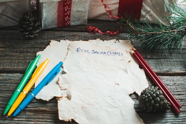 Uma carta para o papai noel em um fundo de madeira com galhos de uma árvore de natal
