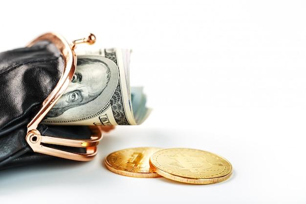 Uma carteira preta aberta com dinheiro, dólares e moedas de bitcoin em uma parede branca.