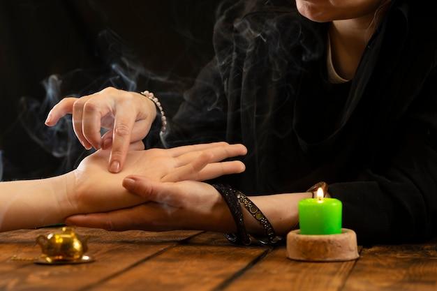 Uma cartomante ou oráculo em busca das linhas do destino na palma da mão de uma pessoa