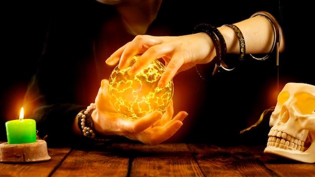 Uma cartomante segura uma bola de fogo nas mãos
