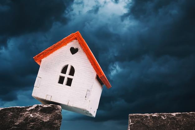 Uma casa de brinquedo em um penhasco de rocha em meio a um conceito de céu sombrio sobre dívidas pendentes para empréstimos hipotecários