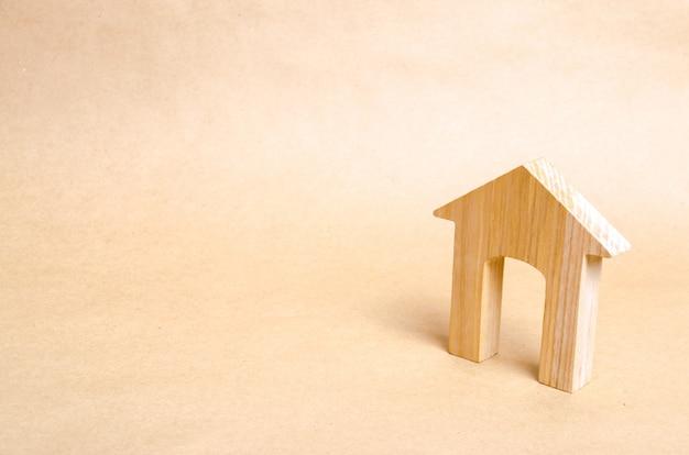 Uma casa de madeira com uma grande porta fica em um fundo de papel bege.