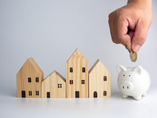 Uma casa de madeira modelo e a mão de um homem segurando uma moeda. conceito de negócio de habitação.