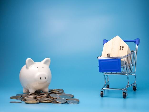 Uma casa de madeira modelo no carrinho de compras com uma pilha de moedas e cofrinho no azul