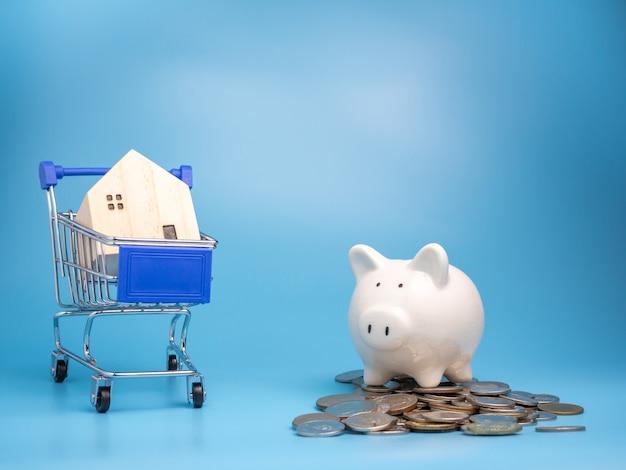 Uma casa de madeira modelo no carrinho de compras com uma pilha de moedas e o cofrinho sobre fundo azul.