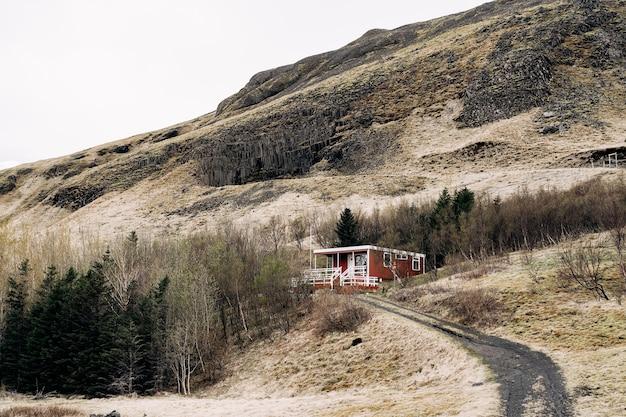 Uma casa de madeira vermelha no sopé de uma montanha na islândia