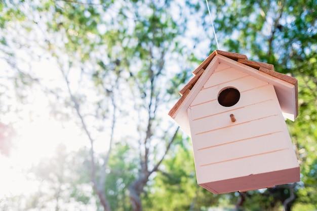 Uma casa de passarinho de madeira com árvores desfocadas e raios de sol.