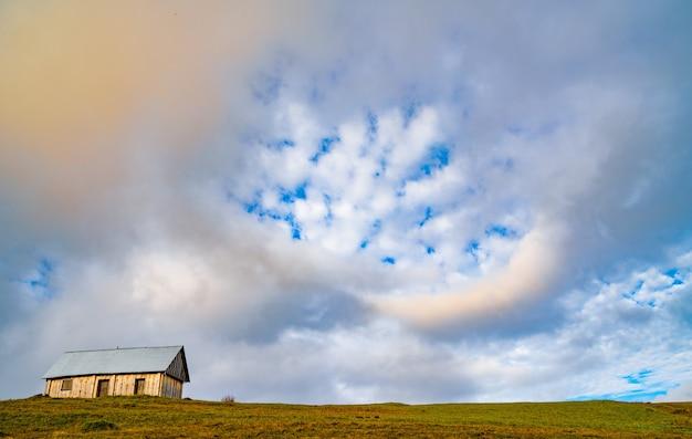 Uma casinha cinza solitária fica em um prado verde úmido e fresco em meio a uma densa névoa cinza