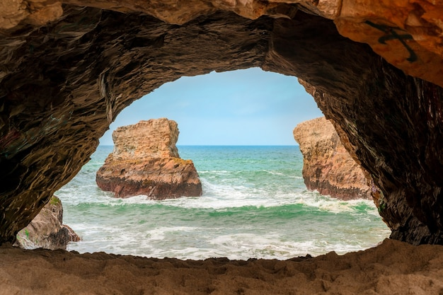 Uma caverna escura com uma vista pitoresca das ondas do oceano pacífico e das rochas da califórnia