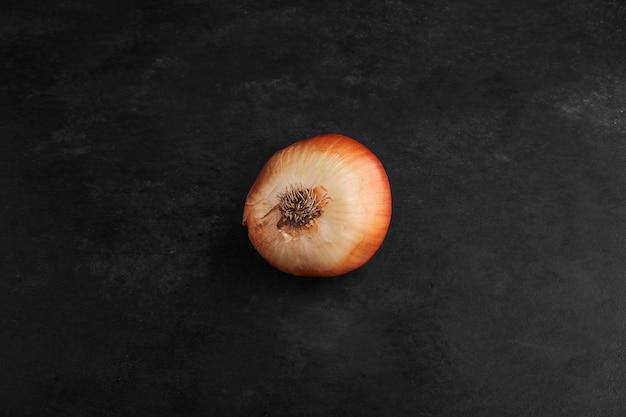 Uma cebola vermelha isolada em um fundo preto.