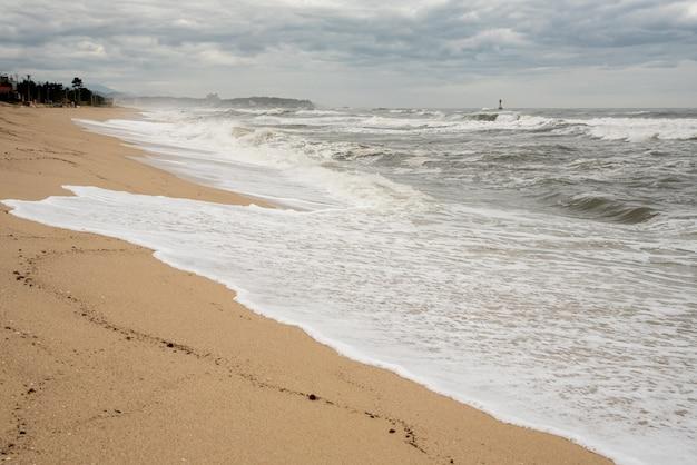 Uma cena à beira-mar em que as ondas altas vêm com tempo nublado e ventos fortes.