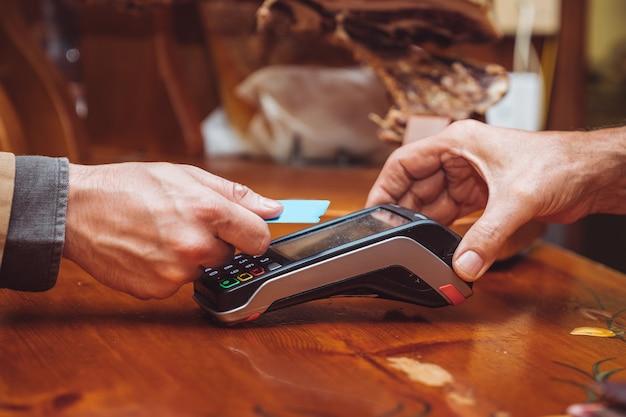 Uma cena de close-up de uma pessoa pagando sem contato com cartão
