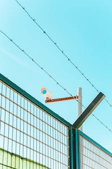 Uma cena minimalista e colorida de uma câmera de vigilância com uma parede e um arame farpado